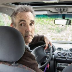 Man turning to look while backing up car