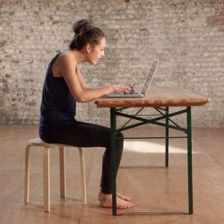 Woman sitting hunched over computer