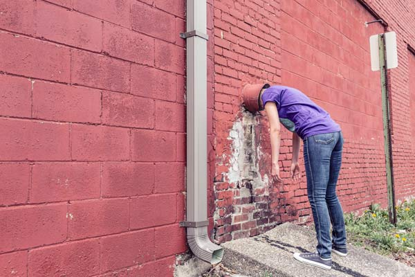 Person with head stuck in a wall