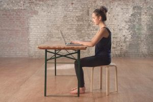 Woman sitting effortlessly at computer