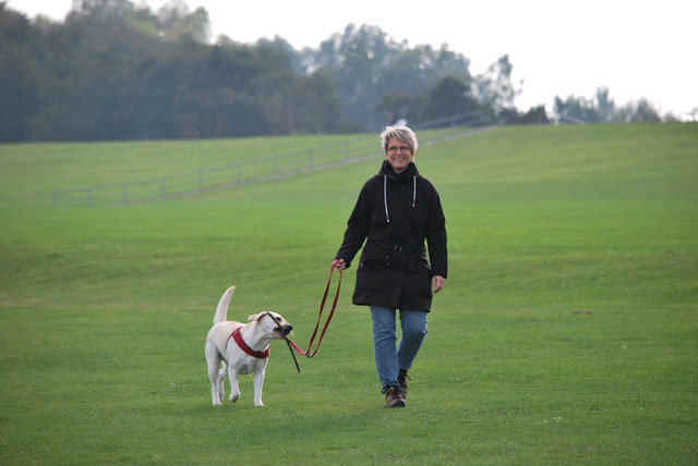 Happy, healthy woman walks dog