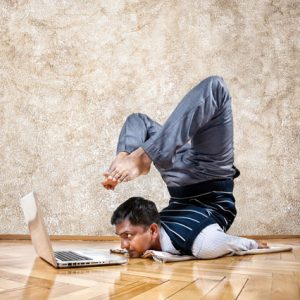 Man doing yoga pose at the computer